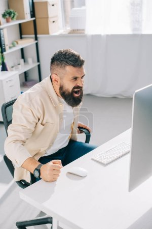 Impulsive businessman sitting in office chair, screaming and beating fist on desk