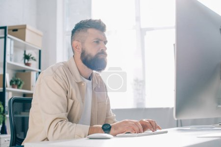 concentrated businessman working at computer desk in office