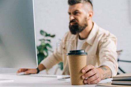 Foto de Hombre enojado sosteniendo la taza de papel café y mirando el monitor de la computadora - Imagen libre de derechos