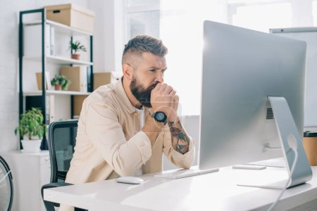 thoughtful businessman with clenched hands sitting at computer desk