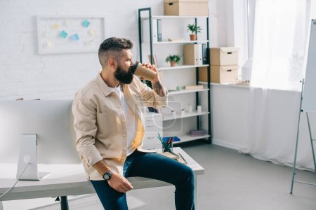 Photo for Bearded businessman sitting on office desk and drinking coffee from disposable cup - Royalty Free Image