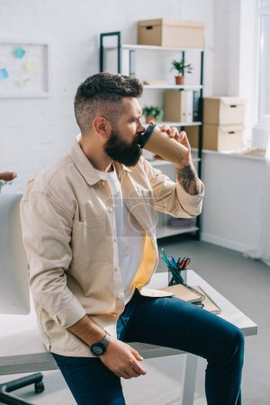 Photo for Bearded businessman sitting on desk and drinking coffee from paper cup in office - Royalty Free Image