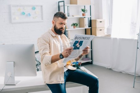 Casual businessman sitting and reading newspaper in modern office