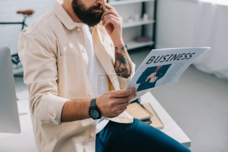 Businessman sitting and reading newspaper in modern office