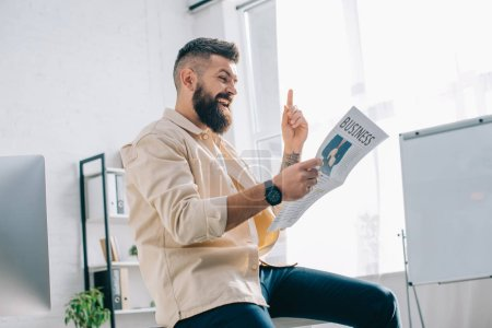 Cheerful businessman reading newspaper in modern office