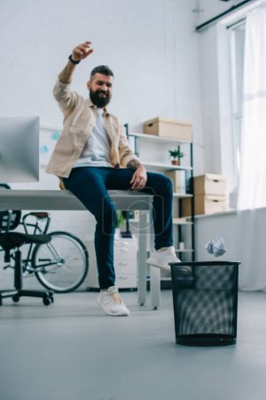 Cheerful man throwing paper in bin in modern office