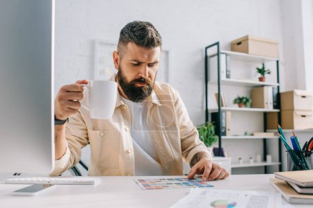 Male designer sitting with white cup of tea and looking at palette in office