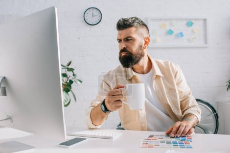 Handsome designer drinking beverage and looking at computer monitor in modern office