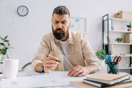 Photo for Bearded architect working on blueprints in modern office - Royalty Free Image