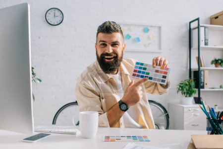 Bearded designer gesturing at color palette in modern office