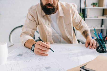 Photo for Bearded architect sitting at desk and working with blueprints - Royalty Free Image