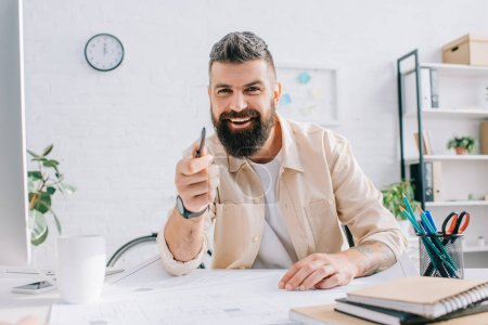 Male architect sitting at desk, gesturing and smiling in office
