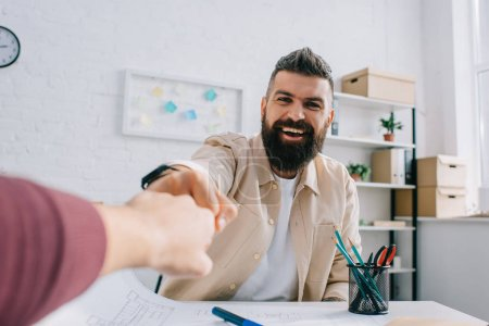 Cheerful architect smiling and giving fist bump to coworker in modern office