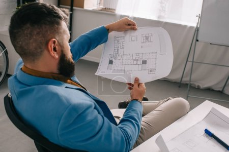 Photo for Male architect sitting and looking at blueprint in modern office - Royalty Free Image