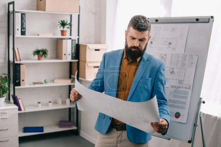 Photo for Handsome architect standing and looking at paper in modern office - Royalty Free Image