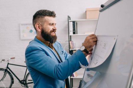 Architekt lächelt und legt Bauplan auf Bürobrett