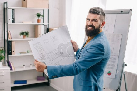 Handsome architect standing in modern office with blueprint