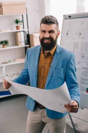 Architecte beau sourire et tenant plan de bureau moderne