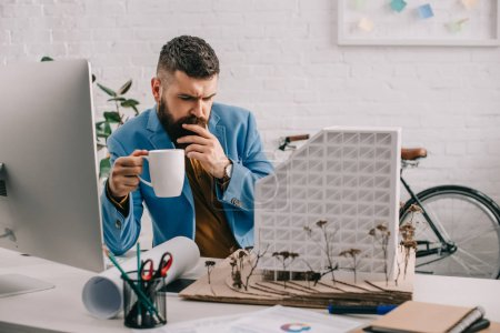 focused adult male architect in formal wear holding cup of coffee and working on project in office