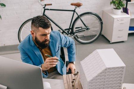 Photo pour Occupé architecte mâle adulte en vêtements travaillant sur le projet au bureau d'ordinateur de bureau - image libre de droit