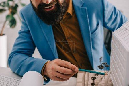 vue recadrée de souriant architecte masculin adulte en tenue formelle pointant vers le modèle de la maison et travaillant sur le projet
