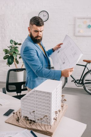 busy adult male architect in formal wear holding blueprint and looking at house model in office