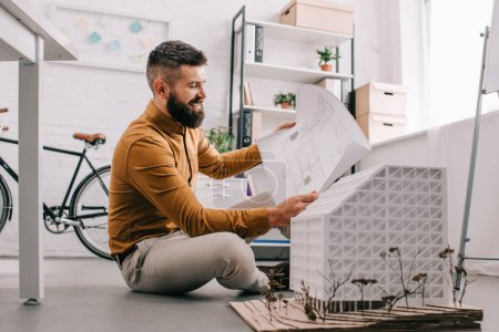 smiling bearded adult male architect working on construction project with house model in office