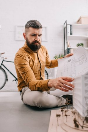 focused bearded adult male architect holding blueprint and working on construction project in office