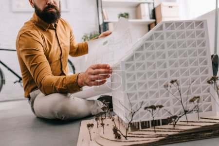Photo for Cropped view of bearded adult male architect holding blueprint and working on construction project in office - Royalty Free Image