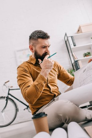 pensive bearded adult male architect holding blueprint and working on project in office