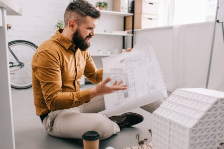 angry bearded adult male architect holding blueprint and working on project in office