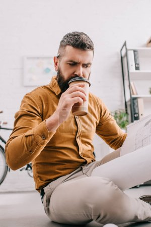 portrait of bearded adult male architect drinking coffee to go and working on blueprint in office