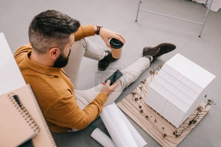 angle view of bearded adult male architect using smartphone, holding coffee to go and working on blueprints in office