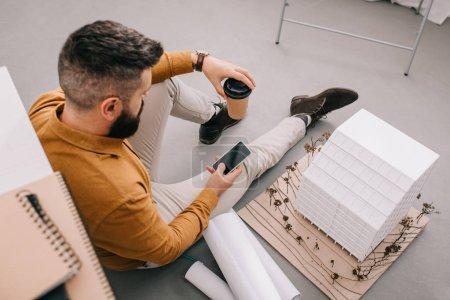 Photo pour Angle de vue de barbu adulte architecte mâle à l'aide de smartphone, tenant le café pour aller et travailler sur plans en bureau - image libre de droit