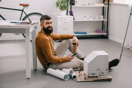 Foto de Sonriendo con barba arquitecto macho adulto con smartphone, celebración de café para llevar y trabajando en planos en oficina - Imagen libre de derechos