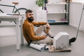 smiling bearded adult male architect using smartphone, holding coffee to go and working on blueprints in office