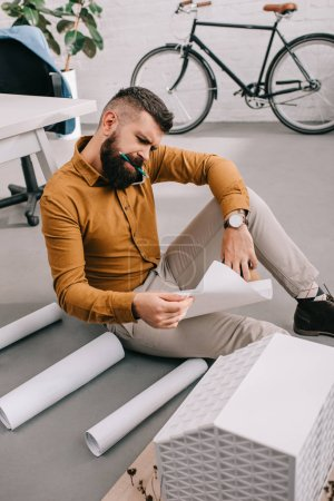 concentrated bearded adult male architect sitting on floor and working on blueprints in office