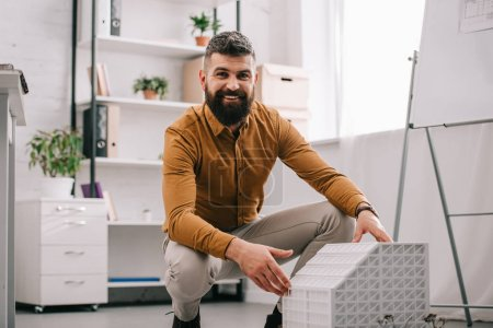 smiling bearded adult male architect looking at camera and presenting house model in office