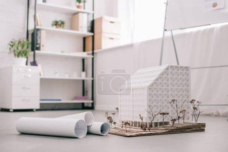 Photo pour Bureau d'architecte moderne avec plans et modèle de maison au premier plan - image libre de droit