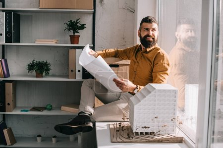 Photo for Smiling bearded adult male architect sitting near house model, holding blueprint and working on project in office - Royalty Free Image