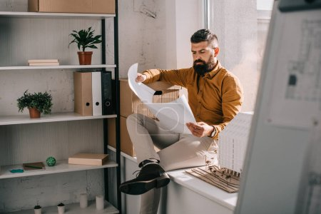 pensive bearded adult male architect sitting near house model, holding blueprint and working on project in office