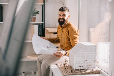 smiling bearded adult male architect sitting near house model, holding blueprint and working on project in office