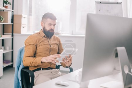 focused adult business man sitting at office desk and using digital tablet at workplace