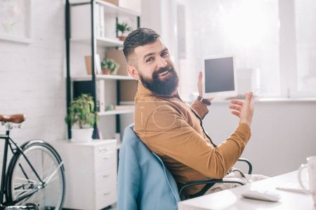 handsome adult business man sitting at office desk and using digital tablet at workplace