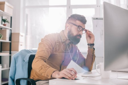 Photo for Serious bearded adult businessman in earphones sitting and working at computer desk in office - Royalty Free Image