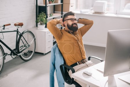 Photo for Smiling bearded adult businessman in earphones with hands behind head sitting and relaxing at computer desk in office - Royalty Free Image