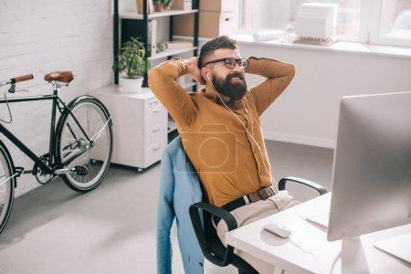 Photo pour Souriant barbu adulte homme d'affaires dans les écouteurs avec les mains derrière la tête, s'asseoir et se détendre au bureau d'ordinateur de bureau - image libre de droit
