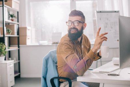 Photo pour Homme d'affaires adulte barbu souriant dans des écouteurs assis et travaillant au bureau de l'ordinateur dans le bureau - image libre de droit