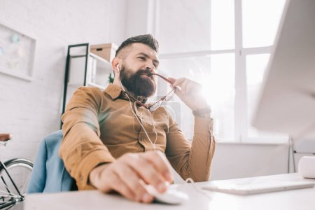pensive bearded adult businessman in earphones sitting and working at computer desk in office