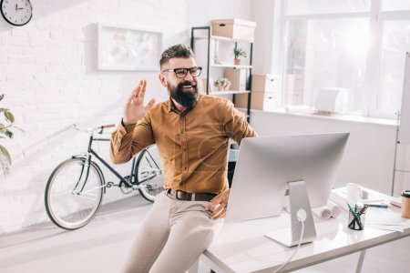 Photo for Cheerful bearded adult businessman sitting at office desk, looking away and waving - Royalty Free Image